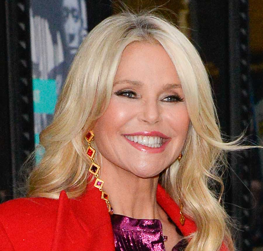 Christie Brinkley smiling, wearing a red coat.