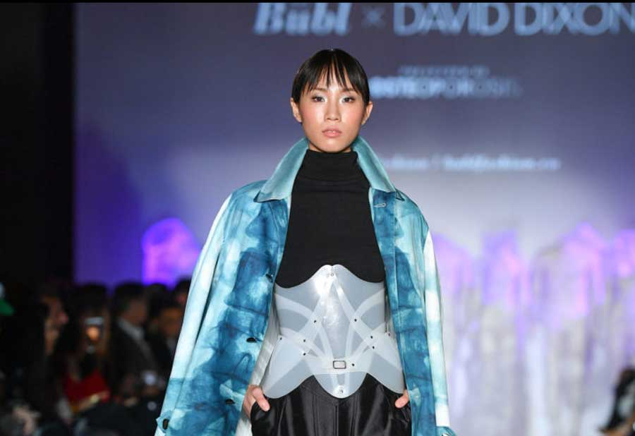 Woman in shiny aqua blue jacket walking the runway.