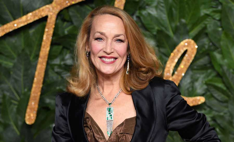 Jerry Hall at fashion week in London, England wearing a brown blouse and black blazer.