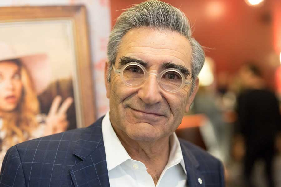 Eugene Levy wearing clear round glasses smirking slightly.