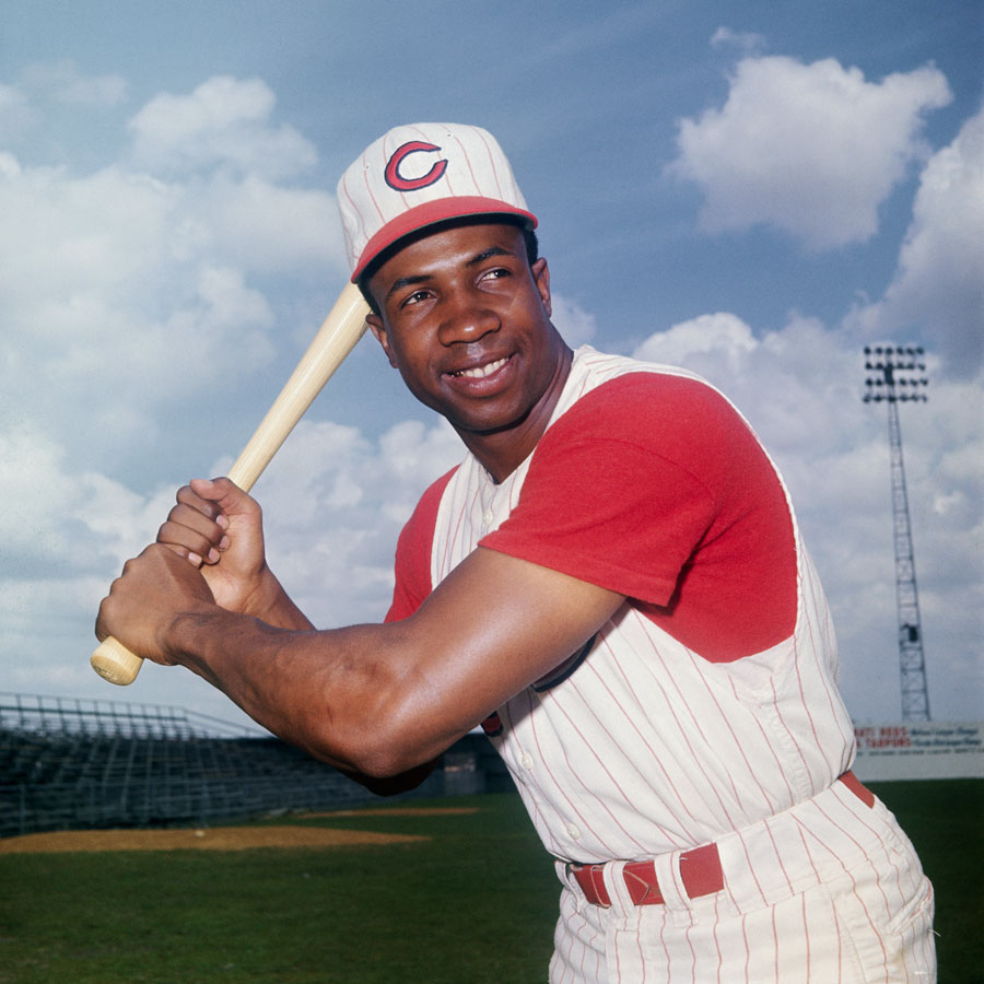 Frank Robinson in a batters stance smiling.
