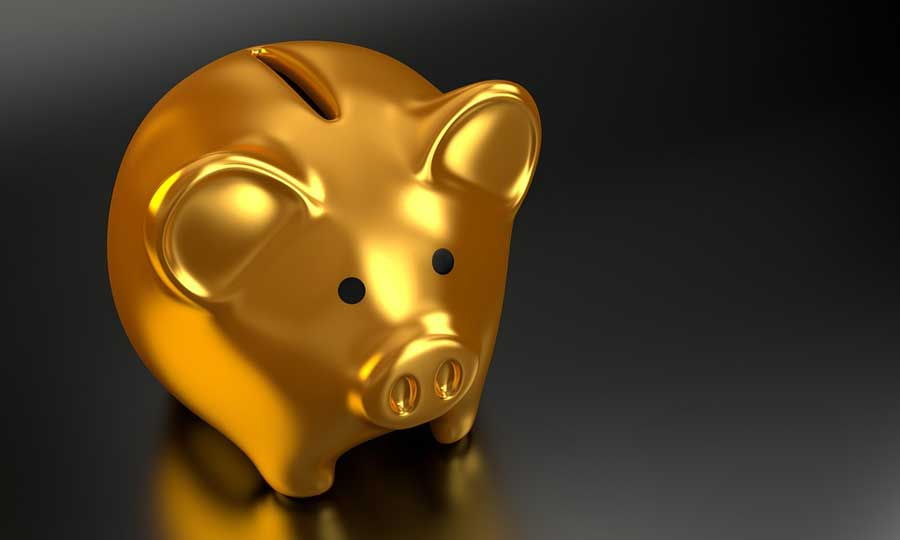 Gold piggy bank on black background.