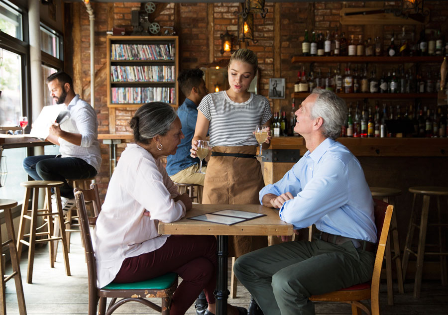 Two older people chat with the server at a coffee shop