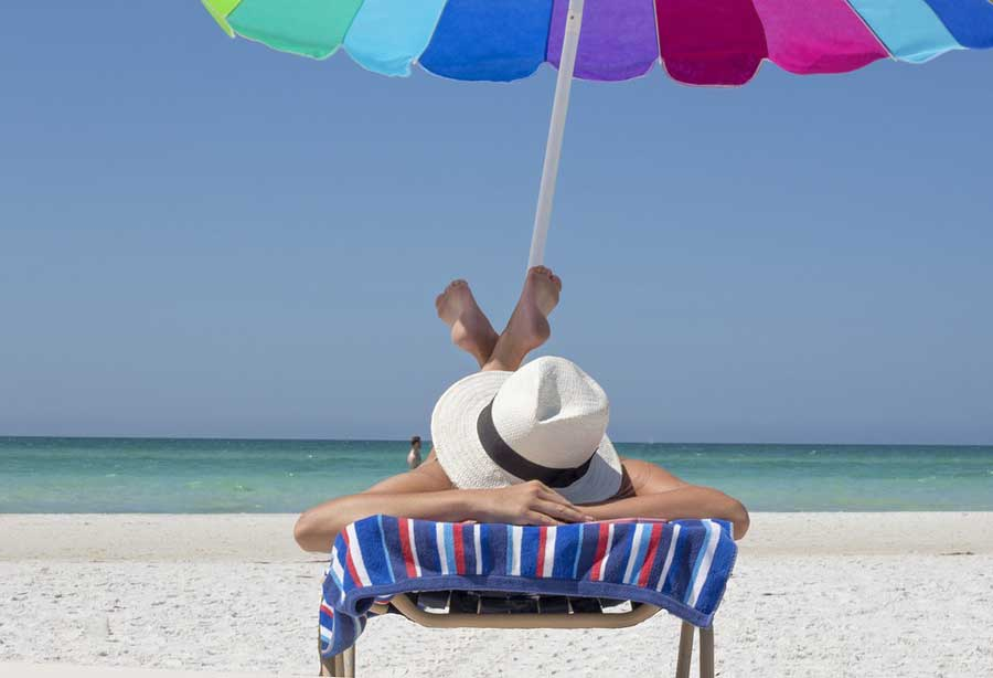 A woman in a sunhat lying on a beach chair facedown.