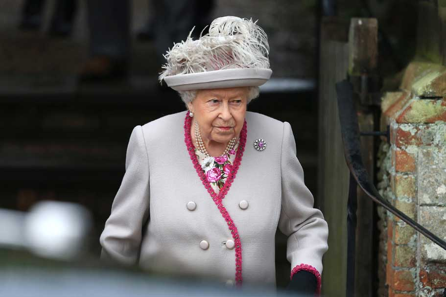 Queen Elizabeth wearing a grey suit and feathered hat.