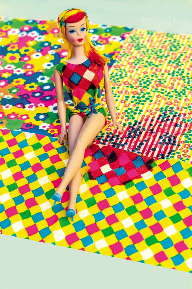 A barbie doll in a colourful bathing suit.
