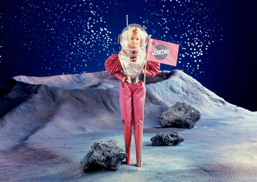 A barbie doll in an astronaut suit holding a flag on the surface of the moon.