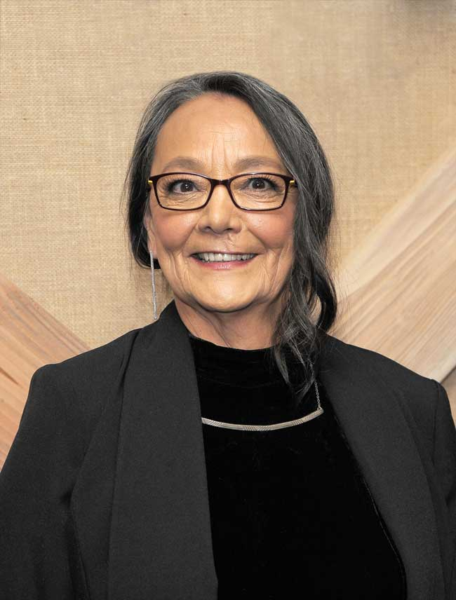 Tantoo Cardinal wearing glasses and a dangly earring, smiling.
