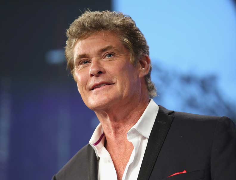 David Hasselhoff smiling, wearing a black suit jacket and a white sure with top two buttons open.