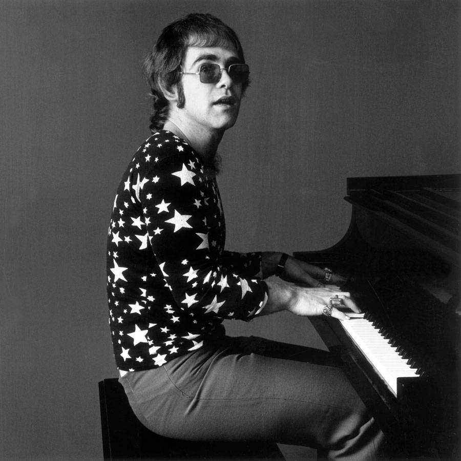 Elton John in his youth playing the piano