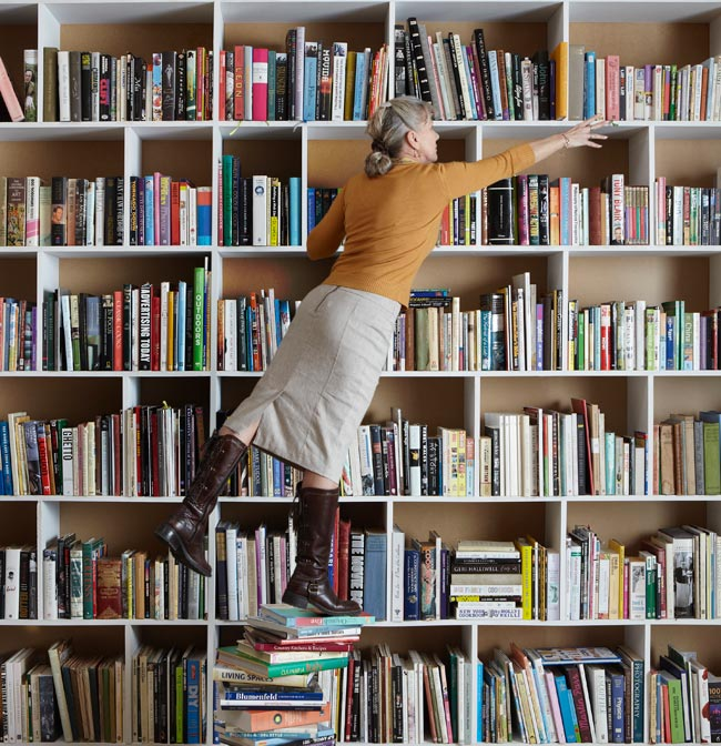 Time to de-clutter. Woman standing on stack of books.