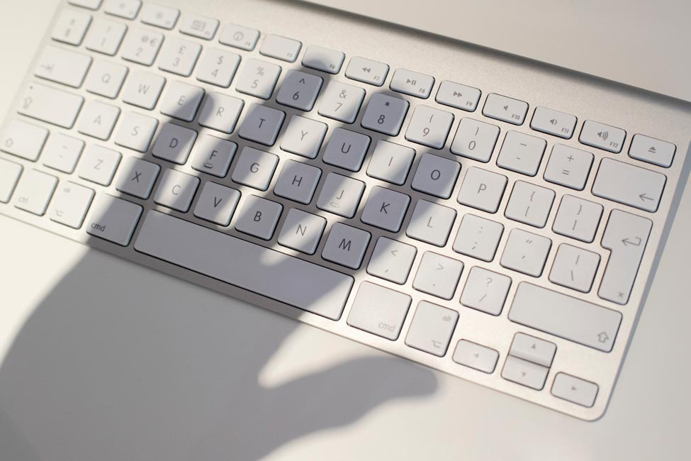 Computer Keyboard with shadow illustrating potential for scams and fraud.