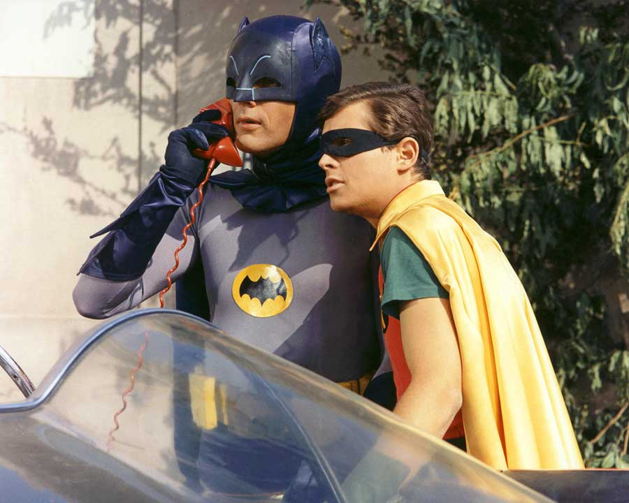 Batman and Robin stand by the batmobile as batman takes a call on the batphone.