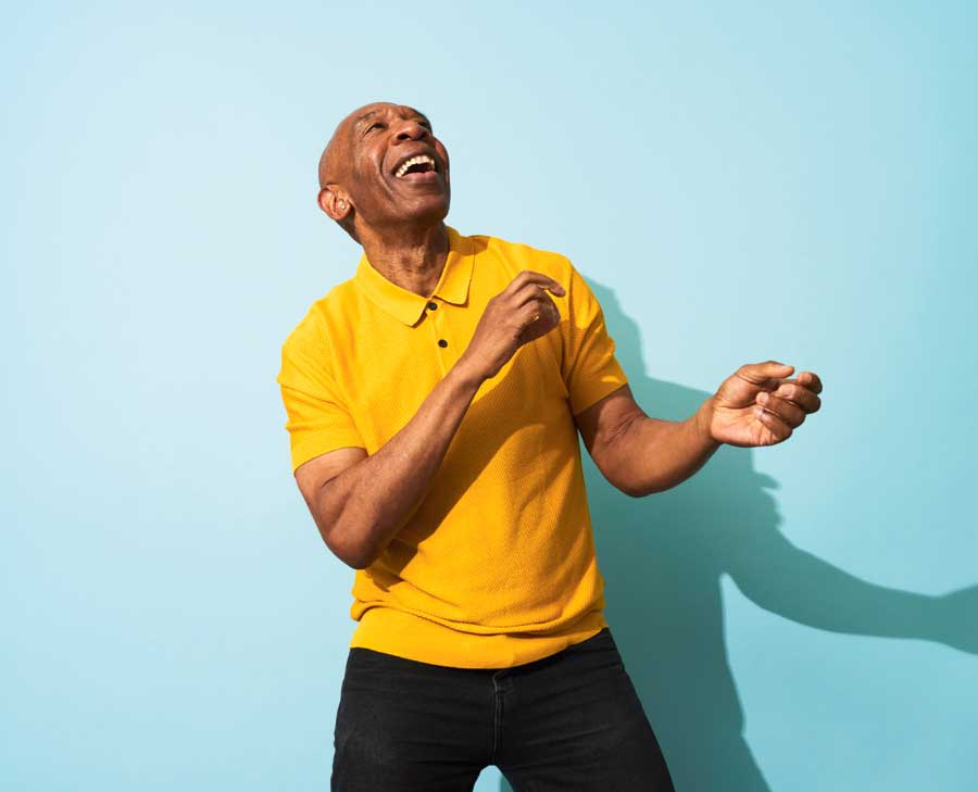 A man in a yellow shirt dancing as he looks upward, smiling.