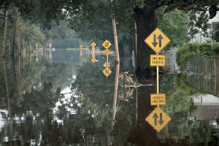 A flooded road with two way traffic signs sticking out from the lake of water.