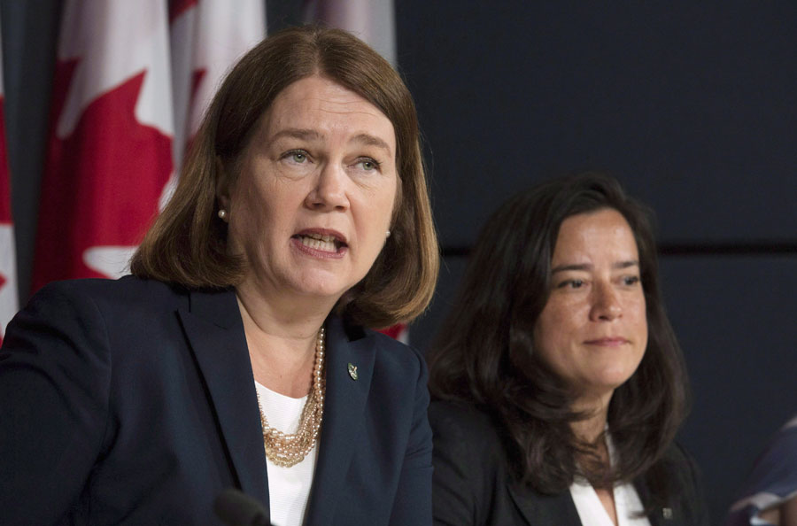 Jane Philpott and Wilson-Raybould side by side with a Canadian flag visible in the background.