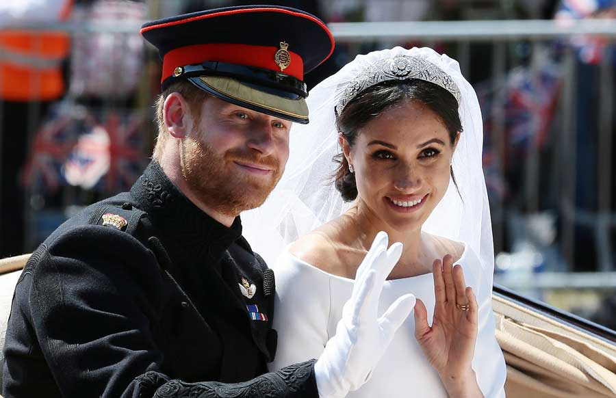 Meghan and Harry wave to fans from a horse and carriage on their wedding day.