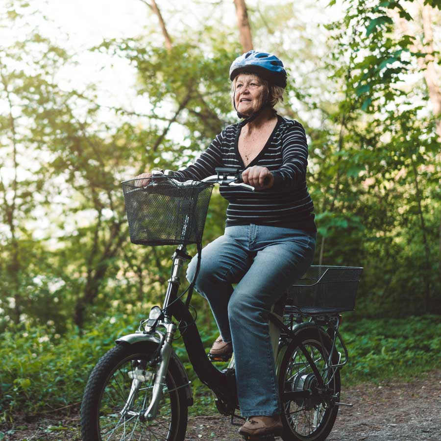 An older woman cycling through a wooded area.