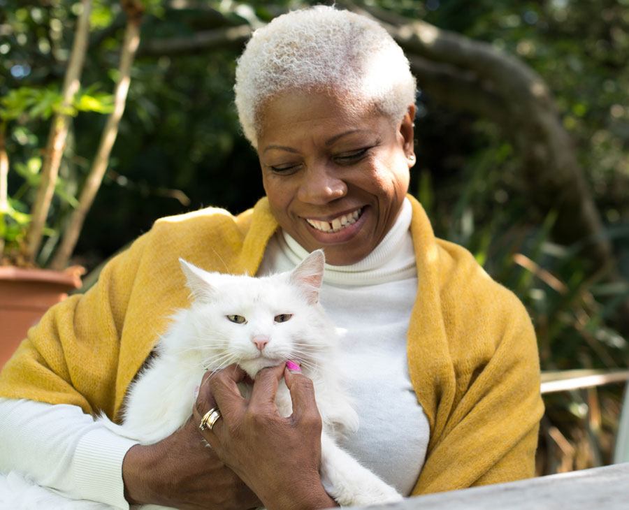 An older woman smiles, holding a cat