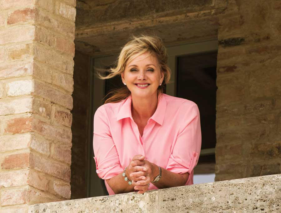 Debbie Travis on her farmhouse balcony leaning on the ledge wearing a pink shirt.