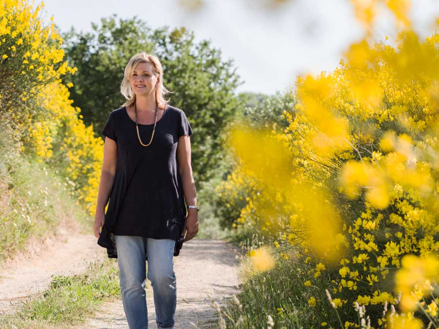 Debbie Travis standing on a path smiling with yellow flowers on each side.