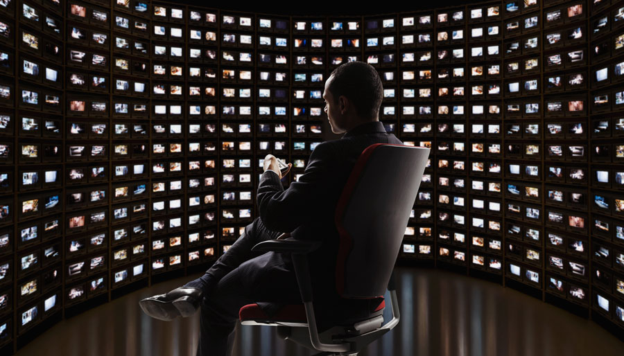 A Man sits in an office chair in front of a wall of TV screens