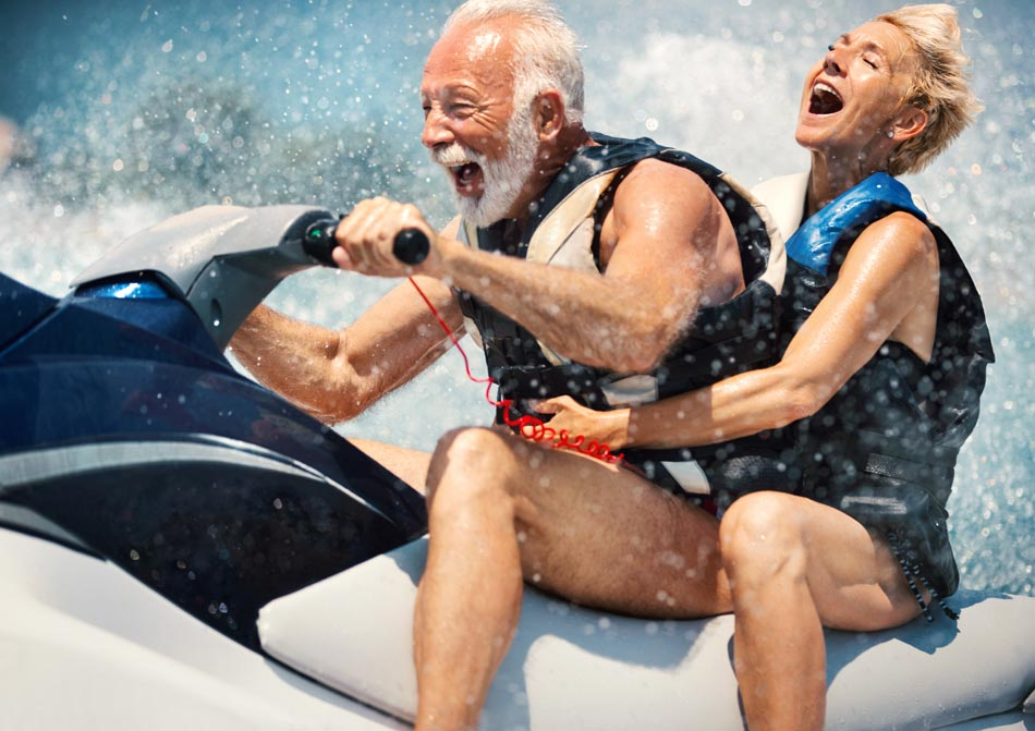 Older couple riding a jet ski