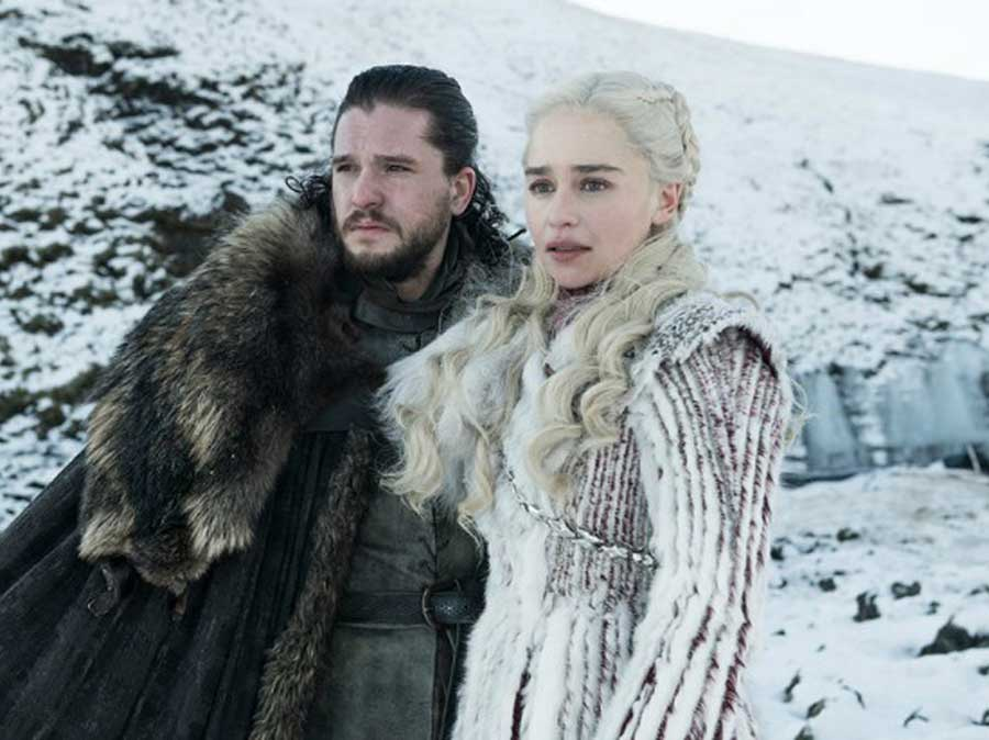 jon snow and Daenerys Targaryen stand side by side on a snow covered mountain.