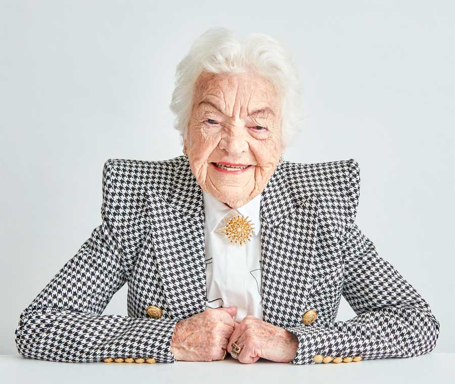 Hazel McCallion resting her forearms on a desk smiling.