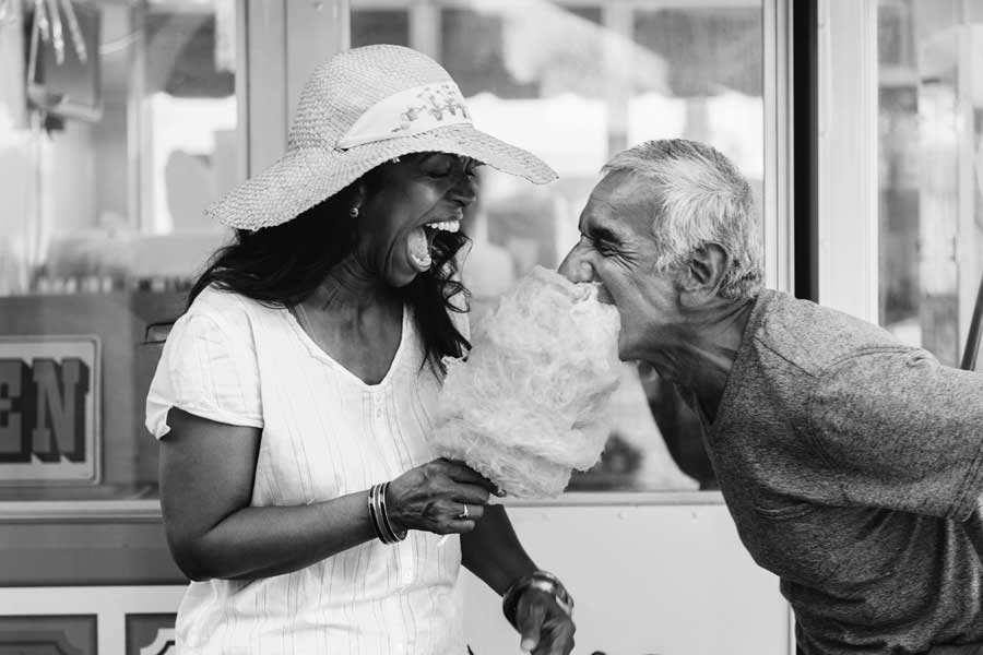 A woman holding a stick of cotton candy laughing as a man bites into it.
