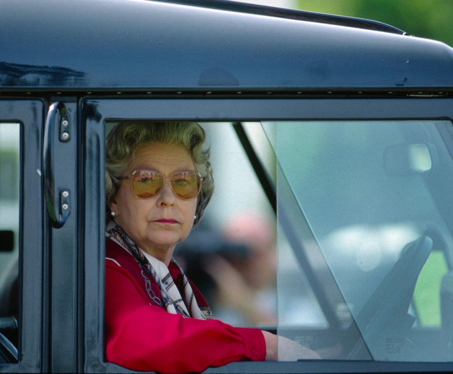 Queen Elizabeth II sitting at the wheel of her four wheel drive Land Rover car watching people competing at the Royal Windsor Horse Show.