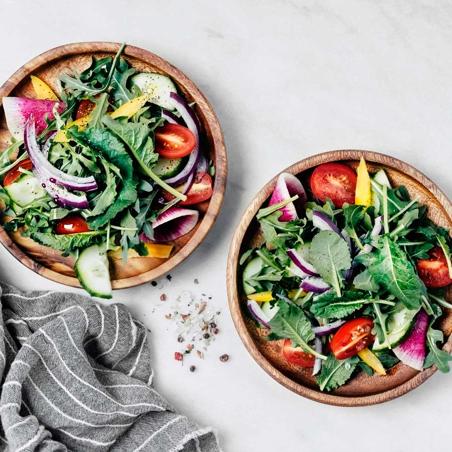 Two wooden bowls of salad.