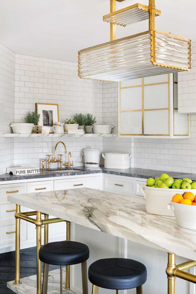 A mostly white kitchen with a marble island and gold accents.