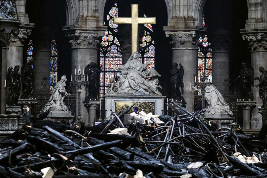 A pile of burnt debris in front of the cross and stained glass windows inside the Notre-Dame Cathedral in Paris.