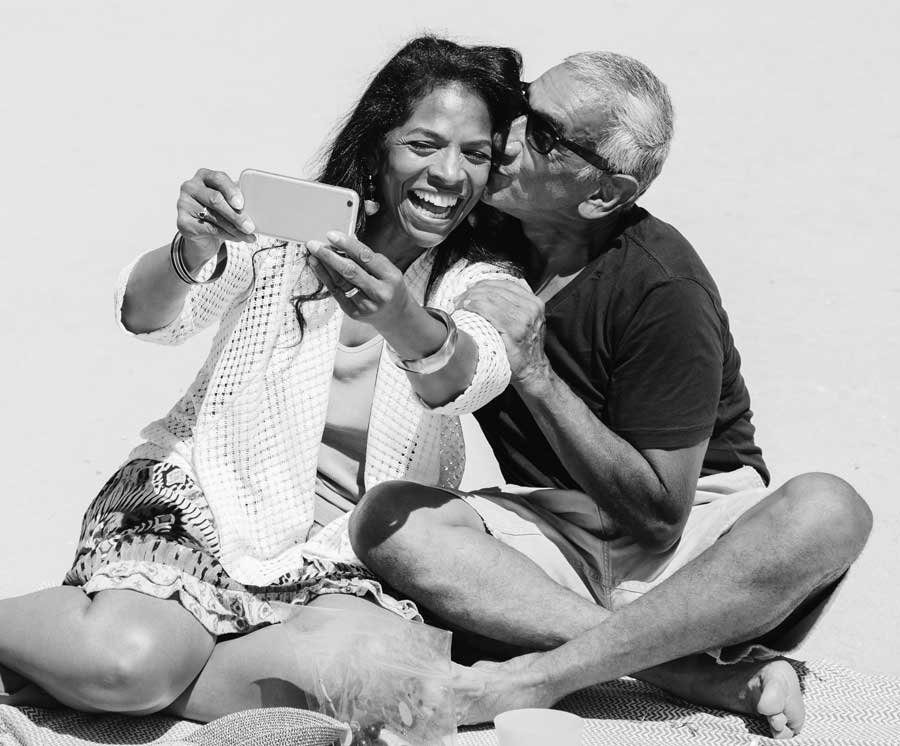 A woman taking a selfie laughing as a man kisses her on the cheek.