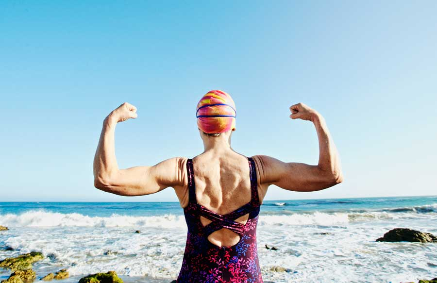 Woman wearing swimming cap faced toward an ocean flexing both of her arms.