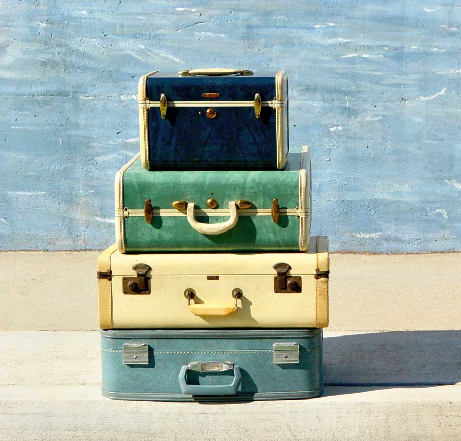 Four suitcases stacked on top of one another.
