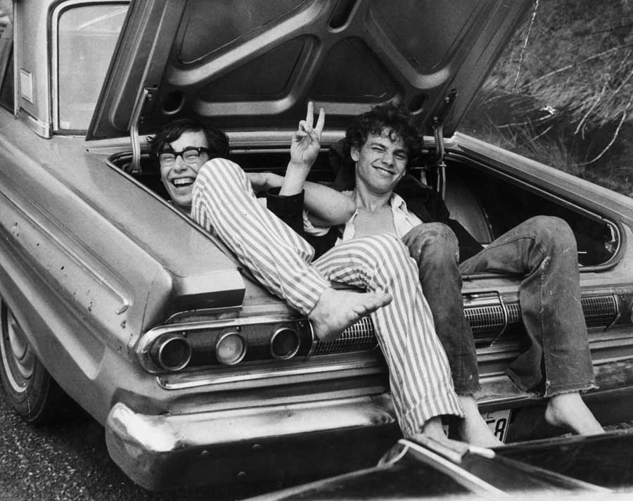 Two young men in the boot of a car after hitching a lift home from the Woodstock Music and Arts Fair.
