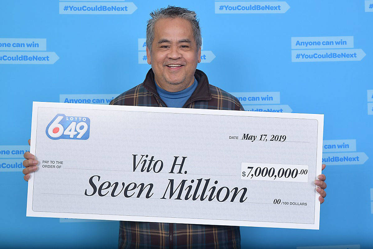 Vito Halasan smiles as he holds up his lottery check for $7 million.