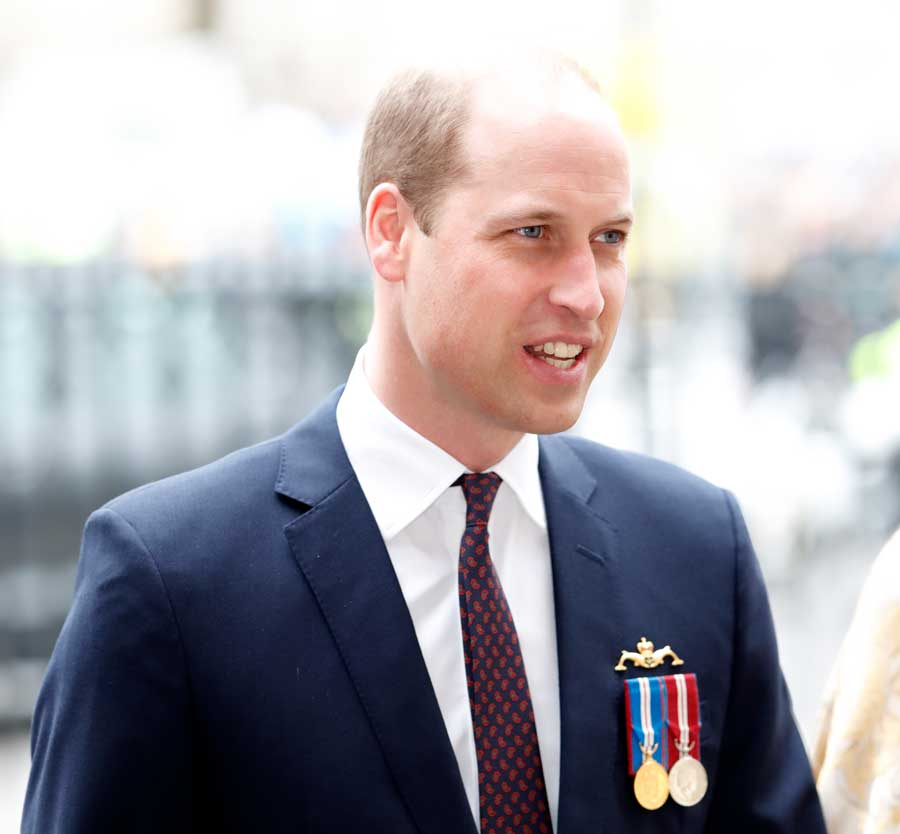 Prince William wearing a dark blue suit jacket and red and blue tie.