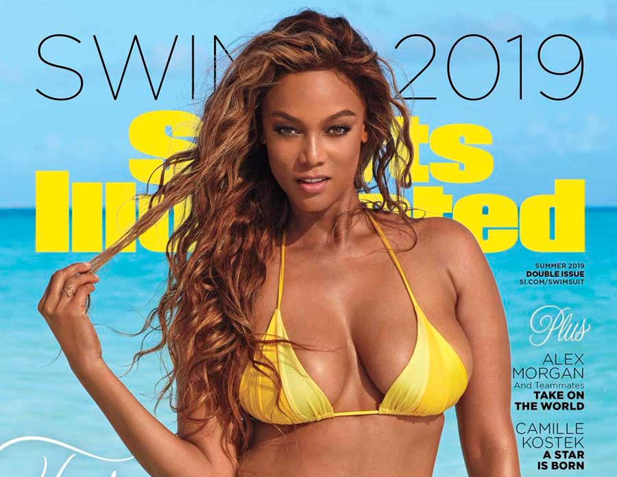 Tyra Banks holding a few strands of hair between her fingers wearing a yellow bikini.