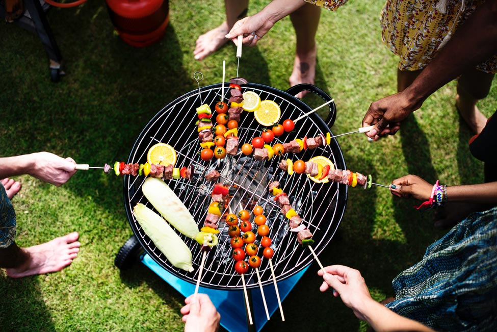 People standing over barbecue