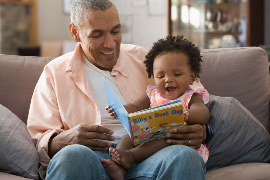 A man with greying hair reading a children's book to a toddler.