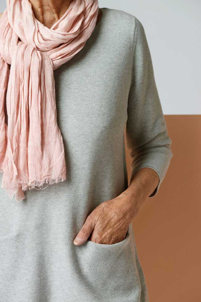 A woman wearing a pink scarf and grey sweater with her hand in the sweater's pocket.