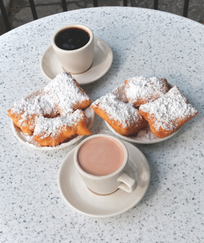 A photo of Beignets and Coffee on a table at Cafe du Monde.