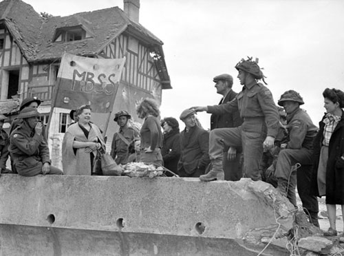 Sgt. Rosaire Gagno talking with French civilians, Bernières-sur-Mer, France, 6 June 1944.