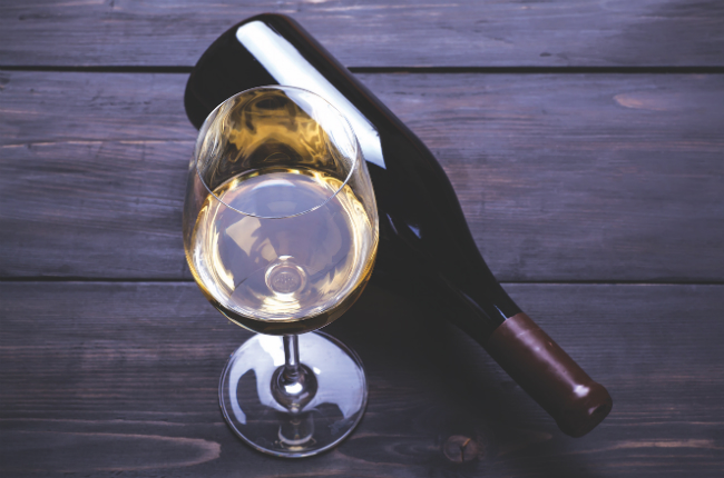 A photo of a glass of white wine with a wine bottle laying on its side next to it.