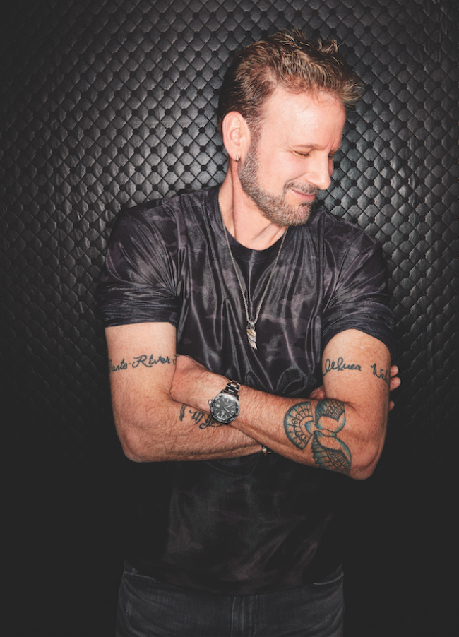 A photo of Corey Hart with his arms crossed.