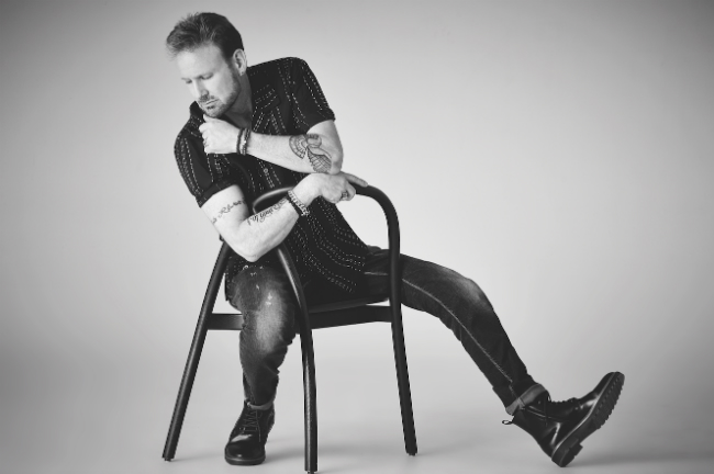 A picture of Corey Hart leaning back in a ming chair with his chin in his hand.
