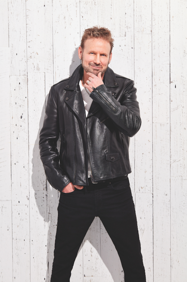 A photo of Corey Hart in a black biker jacket, standing against a white wooden fence.